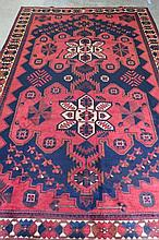 A Luri traditional rug, red ground with Aztec style pattern upon in blue and cream, measuring 314 x 206cm.