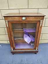 A walnut single door pier cabinet the glazed door opening to reveal compartment within. Brass ornamentation throughout and measuring 77cm diameter.