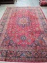 A Najafabad carpet with burgundy ground, 343cm x 244cm.