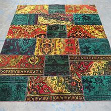 A patched antique rug, yellow and green in colour, measuring 180x150cm
