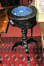 An ebonised display cabinet on tripod support