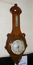 A wall barometer/thermometer in carved oak frame