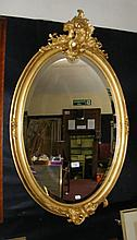 Decorative bevelled oval wall mirror in gilt frame