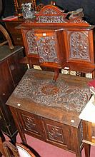 A profusely carved side cabinet with sloped front