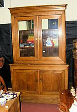 An oak bookcase with glazed upper section and