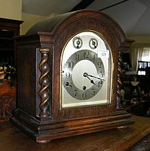 An oak cased striking mantel clock