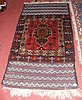 An antique Middle Eastern rug with red ground -
