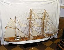 A large wooden model of a three masted boat -