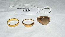 A gold wedding band and two gold signet rings
