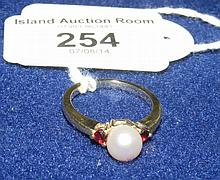 A pearl and garnet ring in 14ct setting