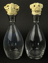 Pair of Modern Glass Decanters With Ivory Figural Animal Head Stoppers. Silvered Tops. Unsigned. Very Good Condition. Measures 11-1/2 Inches Tall. This item will only be shipped domestically and was legally imported into the United States. Shipping