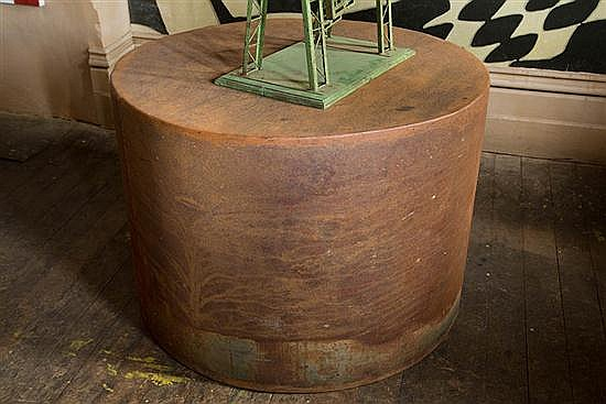 A LARGE CYLINDRICAL CORTEN STEEL DRUM