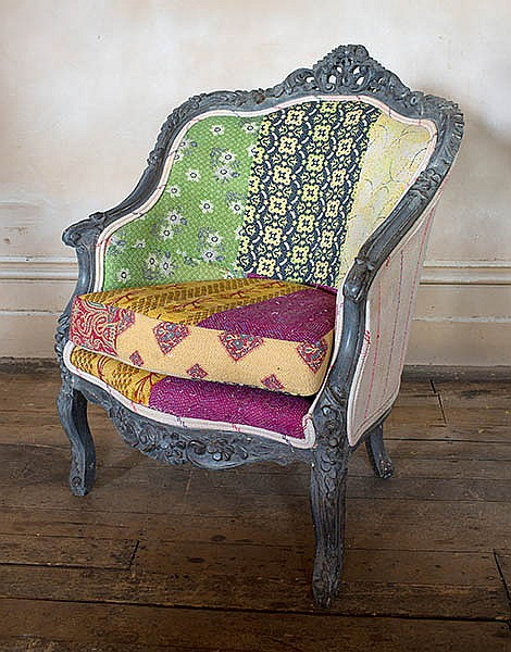 A FRENCH STYLE BERGERE UPHOLSTERED IN HAND-STITCHED COTTON