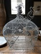 A DECORATIVE WIRE BIRD CAGE FEATURING A SMALL PAINTED MIRROR BY DAVID BROMLEY DEPICTING CHILDREN IN COSTUME