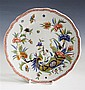 A Rouen polychrome faience plate 18th /19th century, shaped rim with iron red trellis border, decorated with a cornucopia,