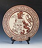 A large Continental copper lustre charger decorated with a heraldic lion in relief bearing a scroll which reads