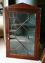 A George III glazed mahogany corner cupboard the single 13 pane astragal glazed door enclosing two mahogany fronted shelves,