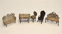 A collection of miniature silver furniture comprising two balloon backed chairs, filigree settee, table and pierced back settee. (5)