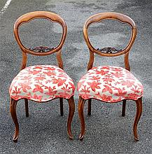 A pair of Victorian walnut balloon back chairs the shaped balloon backs with foliate lower rails, over stuff over seats,
