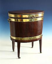 A George III brass bound mahogany cellarette the oval cellarette with brass swing handles and tin liner,