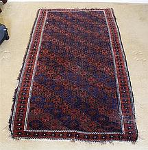 A Turkoman rug with repeating octagonal gol field, worked in red, dark blue and brown, within repeating rosette borders,
