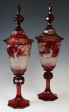 A fine pair of Bohemian ruby flashed goblets and covers the bowls finely cut back to clear frosted glass with stags and deer in forest landscapes the waisted stems with faceted knops on octagonal star cut bases, the covers panelled octagonal, foliate