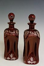 A pair of Bohemian ruby flashed dimpled decanters and stoppers, wheel engraved to the shoulders, corners and bases, with hatched C-scrolls and animals in landscapes, 24 cm high, late 19th Century