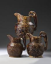 THREE BENNINGTON ROCKINGHAM-GLAZED 'STAG AND BOAR HUNT' HOUND-HANDLED GRADUATED PITCHERS, 1852-67.