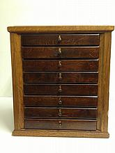 OAK SPOOL CABINET WITH FISHING LURES.