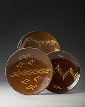 TWO PENNSYLVANIA OR NEW ENGLAND SLIP-DECORATED GLAZED REDWARE PLATES, MID-NINETEENTH CENTURY, AND A THIRD EXAMPLE.