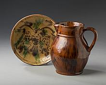 MONTGOMERY, PENNSYLVANIA GLAZED REDWARE PITCHER AND A PLATE, BOTH ATTRIBUTED TO JACOB MEDINGER (1856-1932), CIRCA 1924-32.