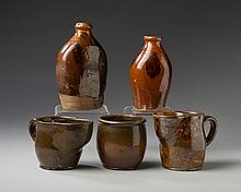 TWO NEW ENGLAND GLAZED REDWARE BOTTLES, TWO SHAVING MUGS AND A JAR, MID-NINETEENTH CENTURY.
