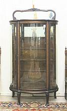 AN OAK AND CURVED GLASS CHINA DISPLAY CABINET,