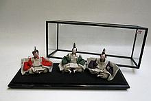 CASED SET OF THREE JAPANESE DOLLS, three seated  male figures each with leather bag, displayed in glass case with footed hardwood frame. Dimensions 22.25