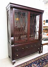 AN EMPIRE REVIVAL MAHOGANY CHINA CABINET, American, early 20th century, featuring a large display cabinet with mullioned glass doors and sides enclosing mahogany shelves, surmounting a 4-drawer base section on scroll feet with casters. Dimensions: