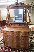LATE VICTORIAN ASH DRESSER WITH ATTACHED TILT MIRROR, American, late 19th century, featuring a lower four-drawer chest with serpentine front, the tilt mirror above with highly carved crest.  Overall dimensions:  76