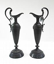 PAIR DECORATIVE SPELTER EWERS mounted on black round stone base, with scrolling handles having  acanthus leaf motif.  Heights 14 inches.