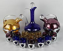 GROUP OF ART DECO FARBER BROTHERS DECANTER AND SHOT GLASS SETS IN COBALT, AMETHYST, AND AMBER GLASS