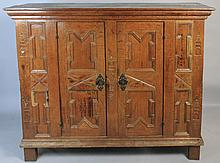 CONTINENTAL BAROQUE OAK PANELLED AND CARVED CABINET