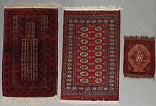 TWO SMALL ORIENTAL RUGS INCLUDING A PRAYER RUG AND A BOKHARA RUG AND A VERY SMALL PAKISTANI RUG
