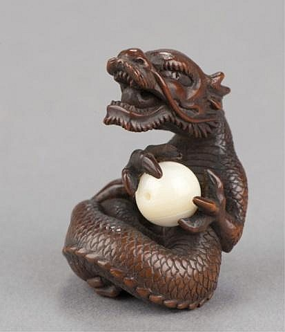 A wood netsuke of a roaring dragon holding a ball.