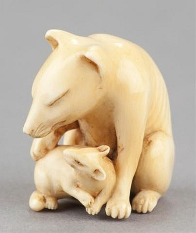 An ivory netsuke of a fox and her cub.