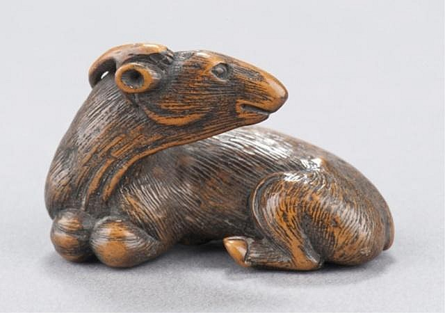 A wood netsuke of a recumbent goat.