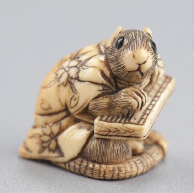 An ivory netsuke of a rat in gown.