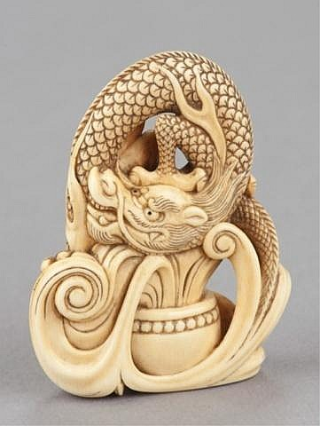 An ivory netsuke of a dragon emerging from an alms