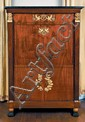 Secrétaire en placage d'acajou ouvrant à un tiroir en ceinture, un abattant et deux portes enserrés entre deux montants de forme gaine surmontés de têtes de grecques en bronze ciselé et doré et terminés par des pieds en pâte de lion en bois noirci et