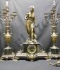 Garniture de cheminée composée d'une pendule reposant sur une base en marbre noir ornée de godrons et rinceaux de bronze accueillant en son centre le cadran aux chiffres romains. Elle est surmontée d'une importante Diane chasseresse en bronze