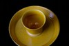 A yellow glazed tea bowl on stand