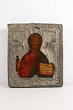 Russian Icon of Christ Pantocrator, finely painted in the traditional style holding the open Gospel and His right hand in blessing against a burnished gilt ground with a diminutive image of a bishop saint flanking His right side. 20th century in a