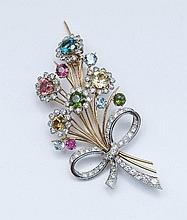18ct yellow and white gold brooch of a spray of flowers in tutti frutti stones, tied with a diamond bow. 8 cm high